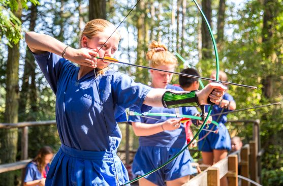 Girls doing archery at summer camp
