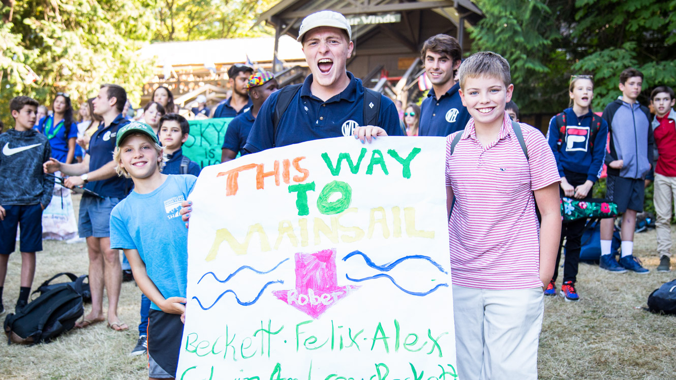 Counselor gathers campers with sign on Arrival Day