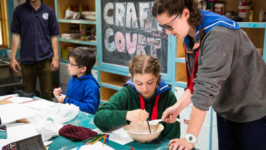 Counselor helps camper with crafts