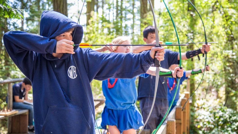 Boys draw bows during camp archery