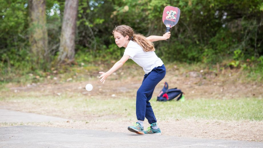 Camper serves during game of pickle ball