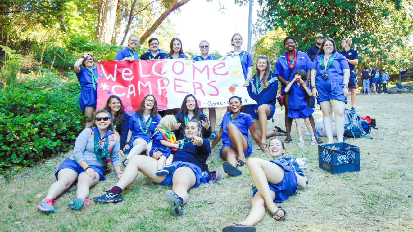 Camp staff sit near Welcome Campers banner