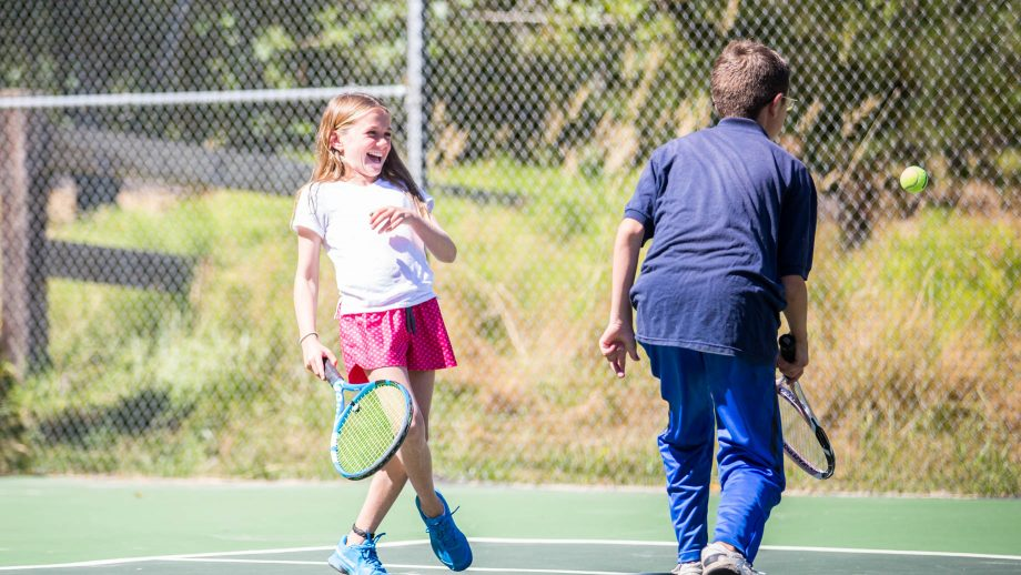 Campers laugh during tennis match