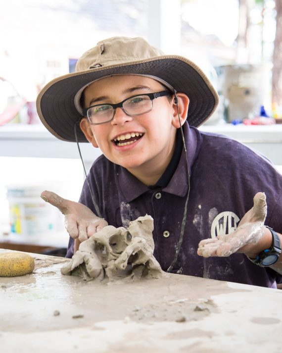 Smiling camper points to lump of clay