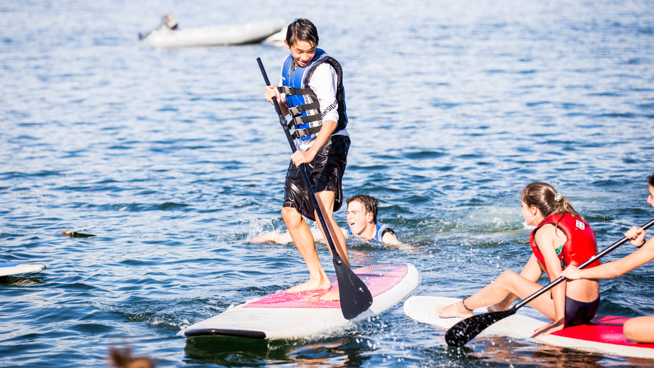 Boy does stand up paddleboarding at summer camp