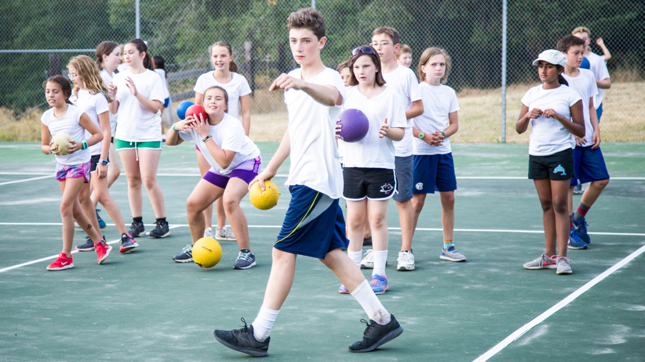 Camper at front of dodgeball group gives directions
