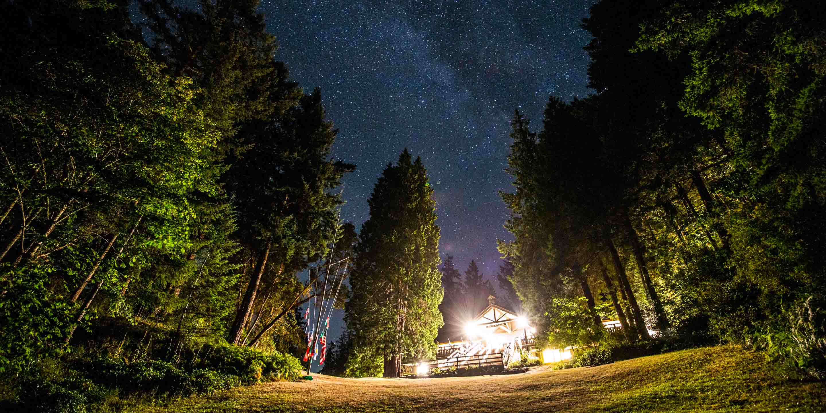 Wide view of Four Winds lodge and stars at night