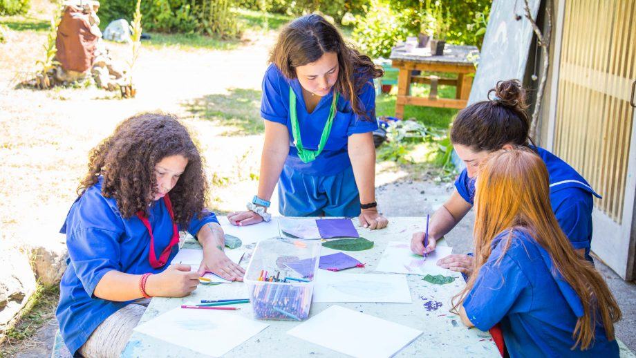 Campers gather around garden table to draw