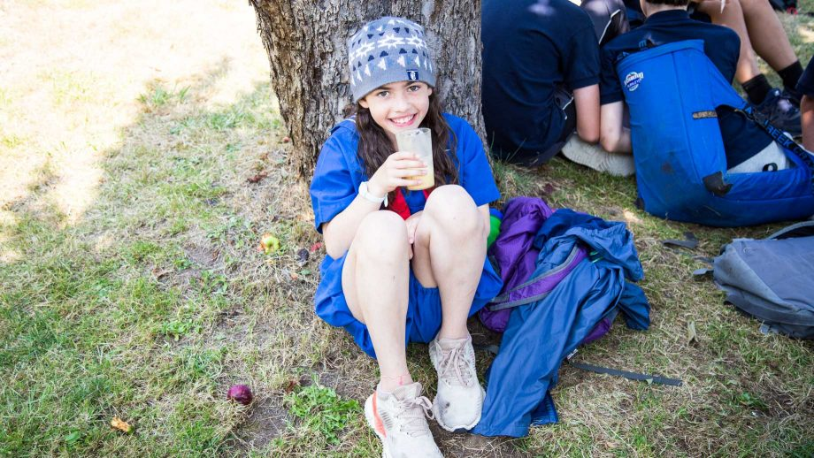 Camper sits under tree with a beverage