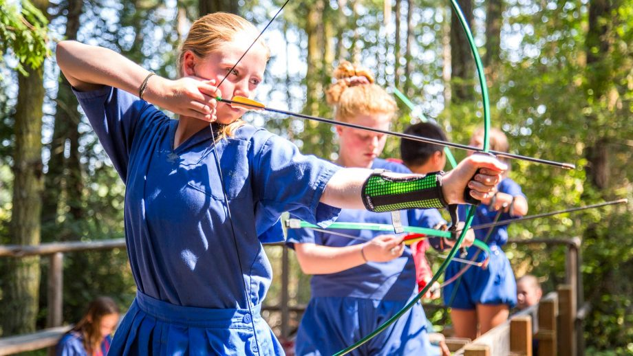 Girls draw bows during camp archery