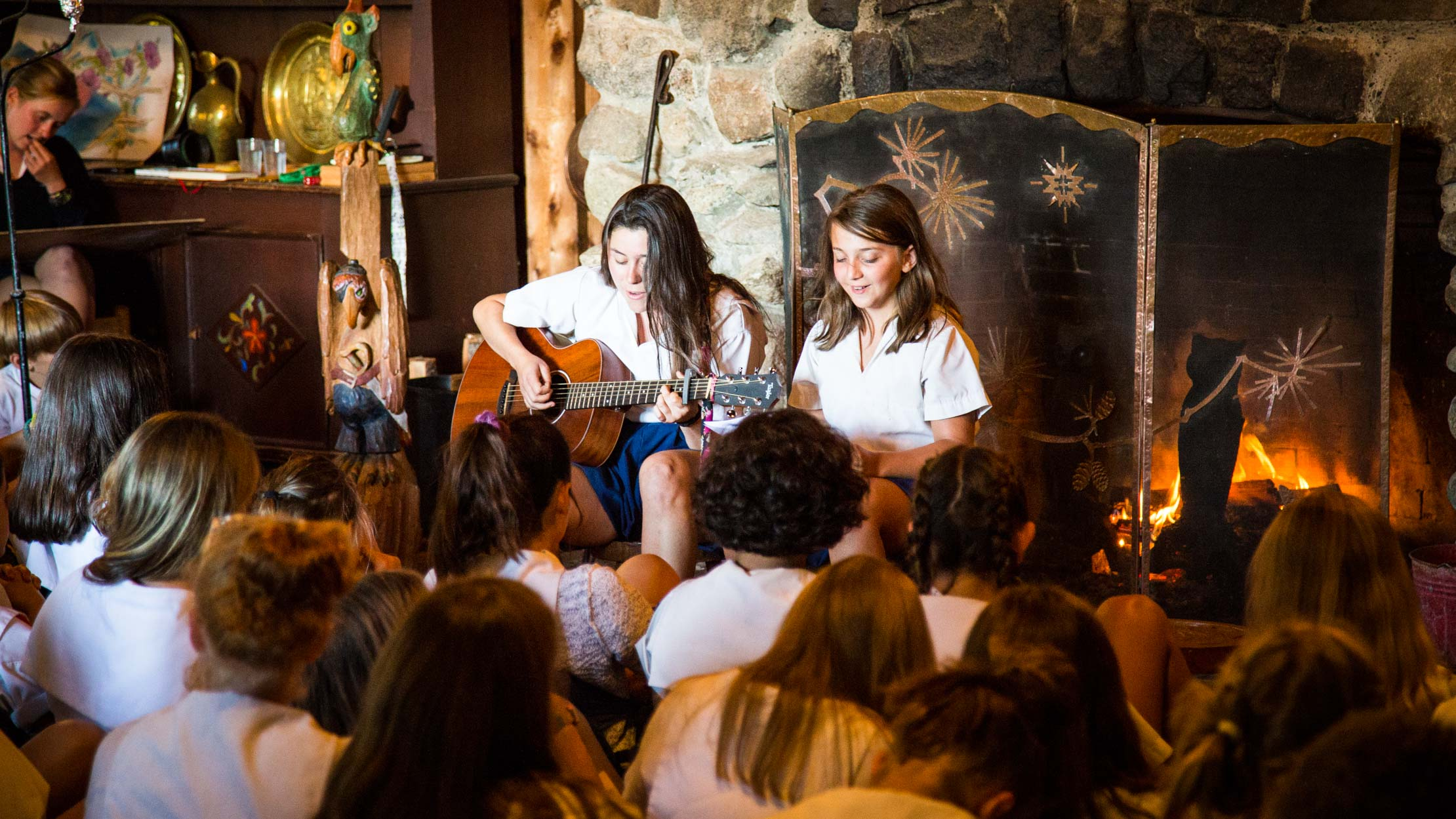 Campers play guitar at evening fire