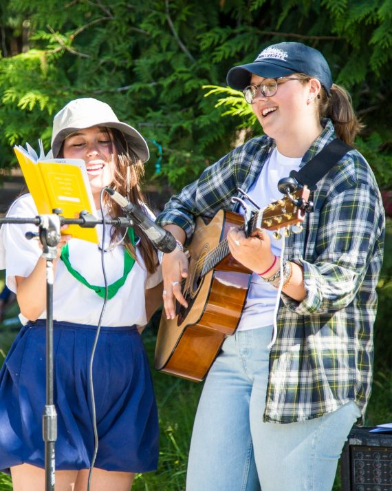 Two girls play guitar and sing at summer camp