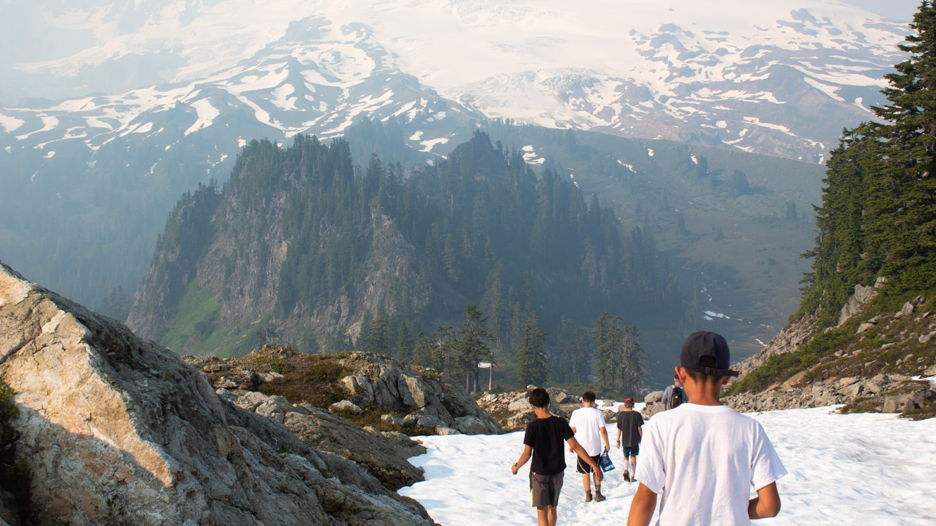 Campers hike down snowy mountain on trip