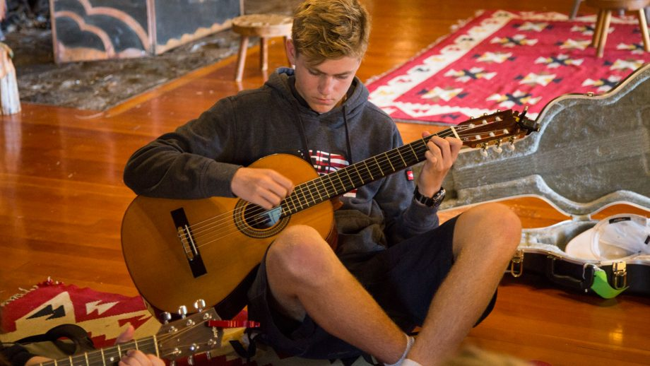 Camper sits on floor with guitar