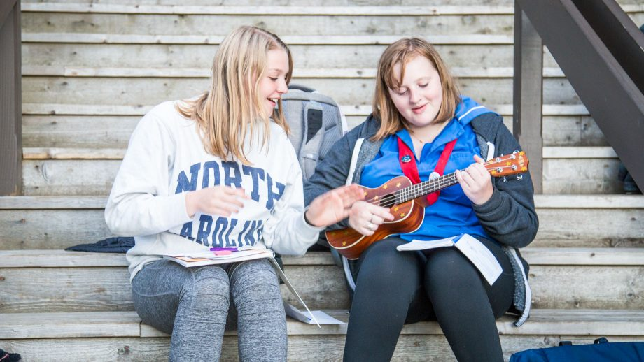 Campers sit on steps to play ukelele