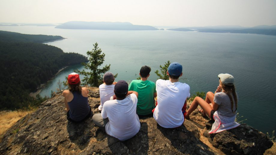 Campers sit on rock outcrop