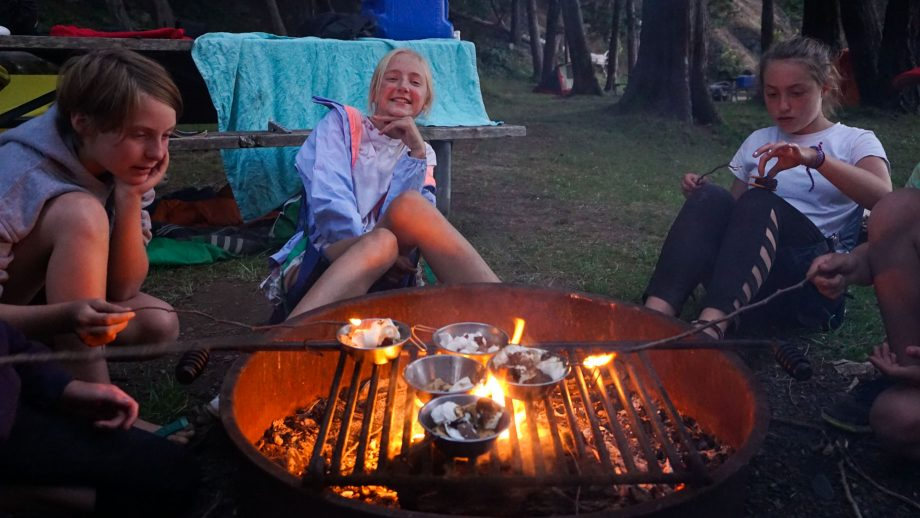Campers cook s'mores over fire