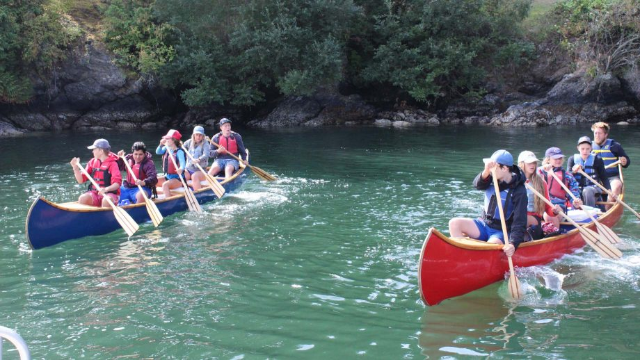 Group of campers paddle two canoes