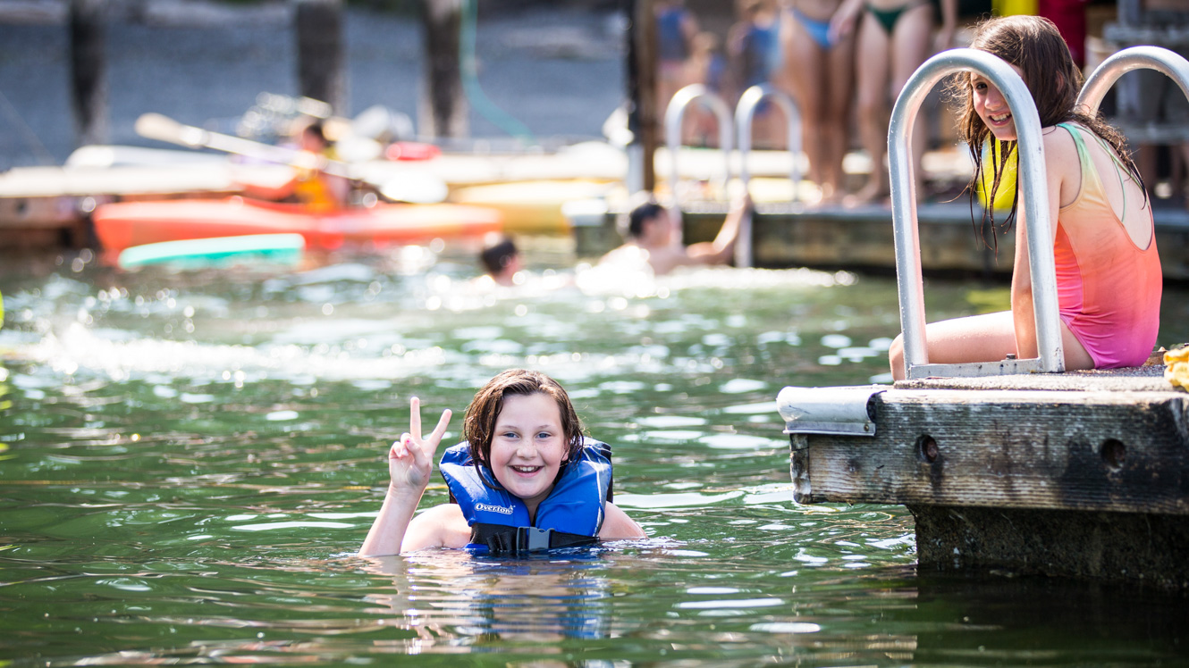 Swimming camper holds up a peace sign