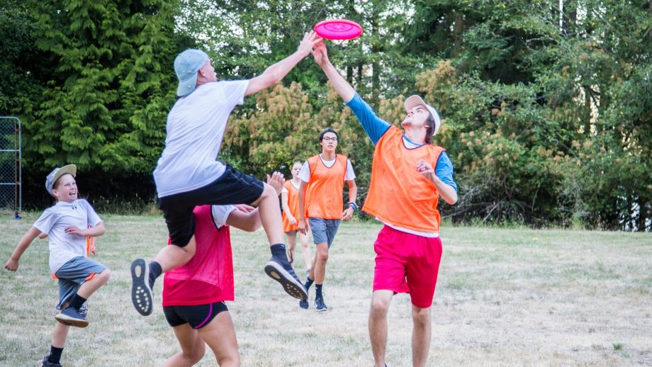 Camper jumps for frisbee during ultimate frisbee game