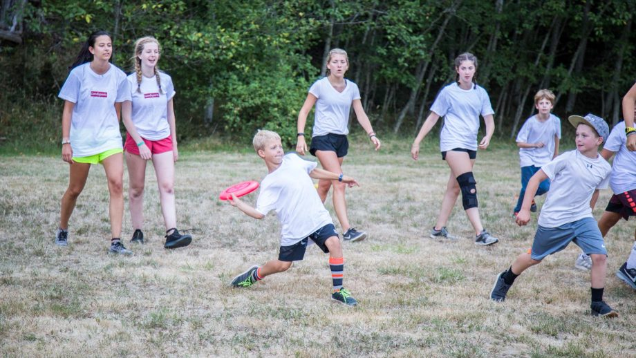 Camper throws frisbee during game