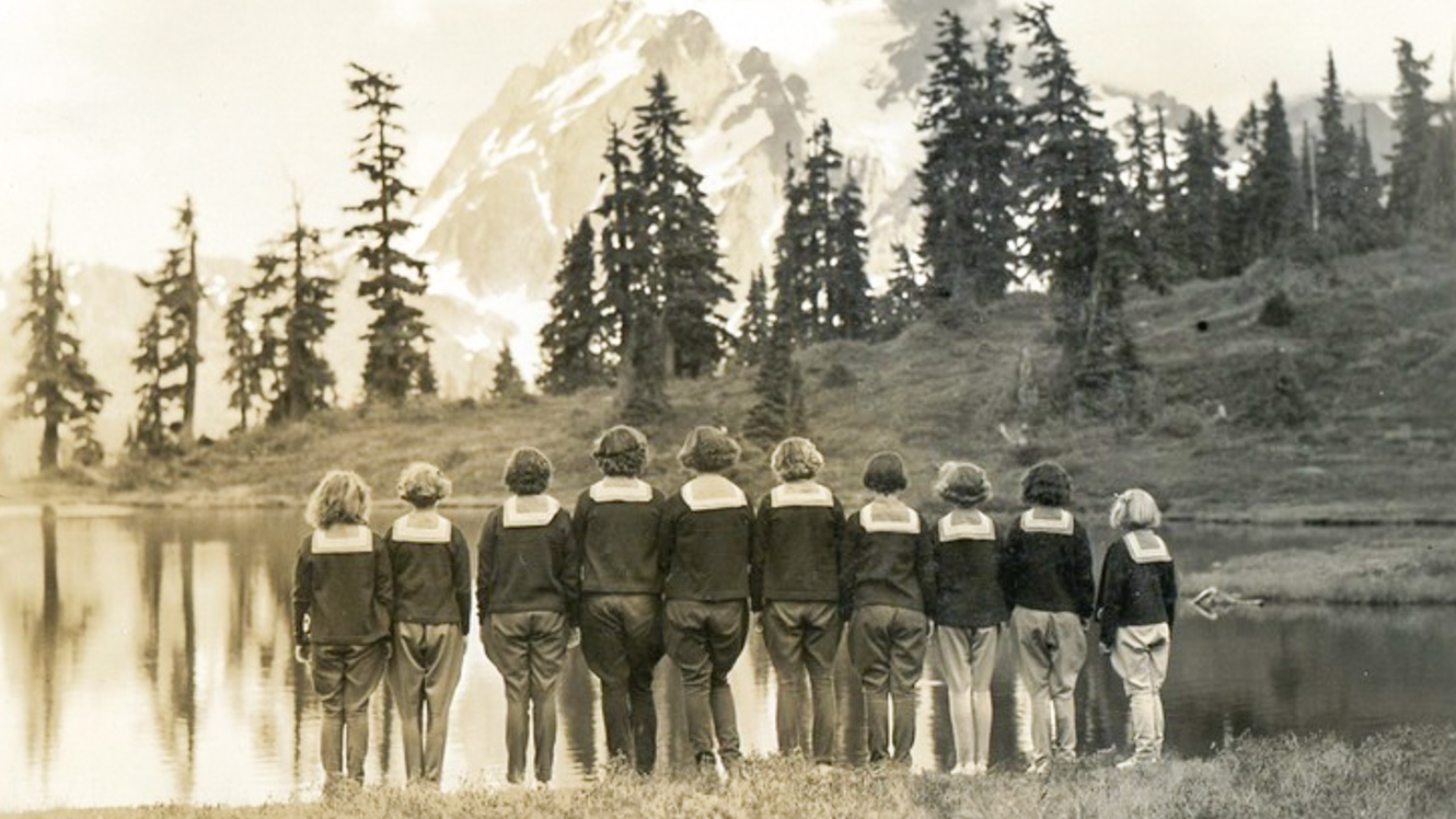 Black and white photo of campers standing near mountain