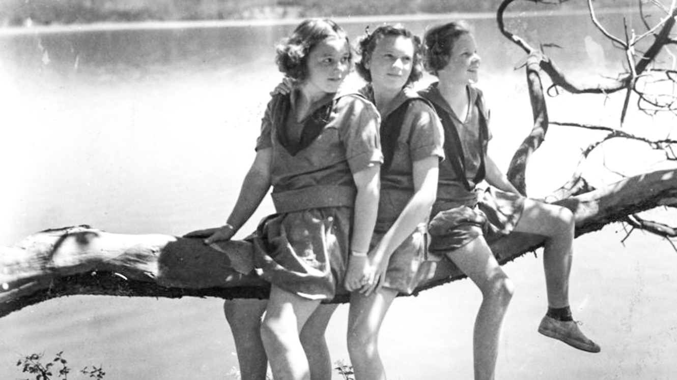 Black and white photo of girls sitting on tree branch
