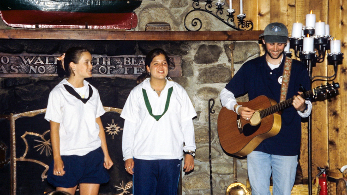 Group of 1990s campers perform with guitar