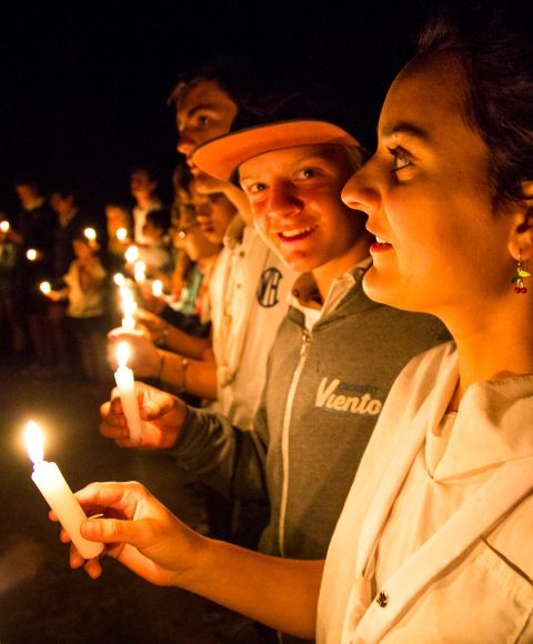 Campers hold candles in evening circle